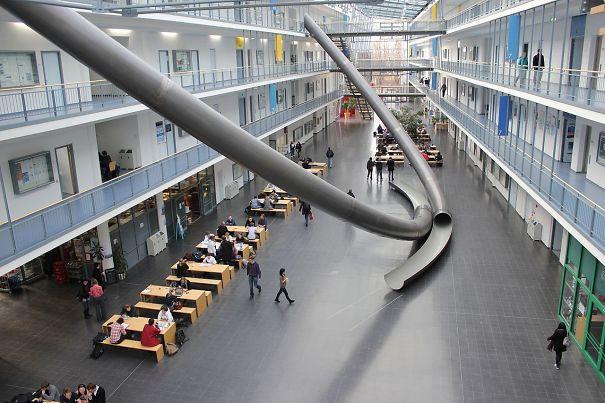Technische school in München heeft glijbanen in het gebouw. Wie is er jaloers?