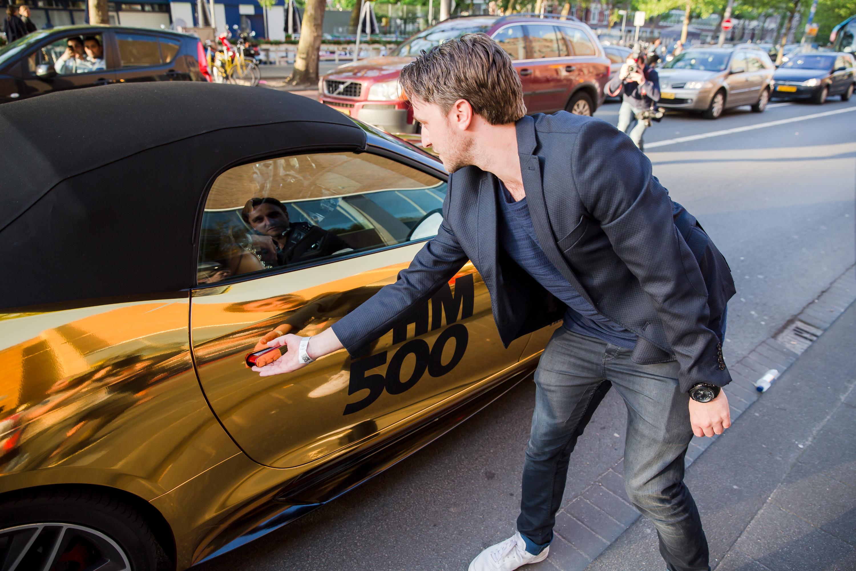 Hoofdredacteur Chris Riemens opent de deur van de gouden Jaguar F-Type